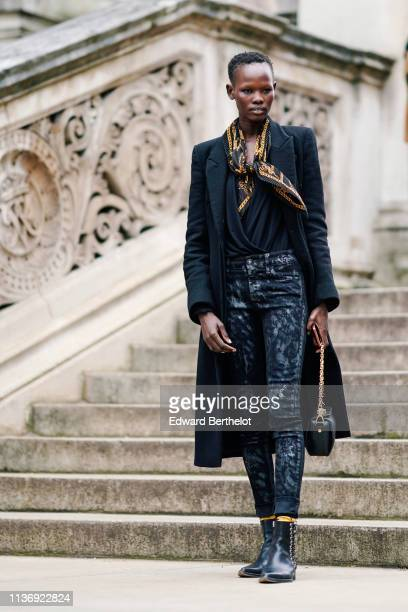 Model wears a black and yellow pleated scarf, a black wrap-over top, a black coat, a navy blue spotted pants, a black bag, black pointy side-laced...