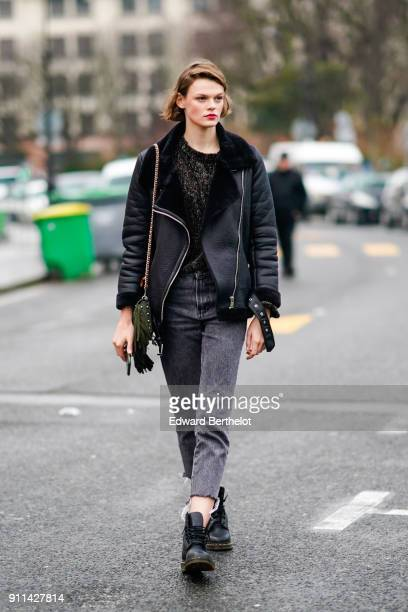 A model wears a black aviator jacket with fur inner lining cropped black jeans pants black leather shoes outside Chanel during Paris Fashion Week...