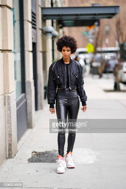 A model wears a black bomber jacket black shiny leggings sneakers during New York Fashion Week Fall Winter 2020 on February 12 2020 in New York City