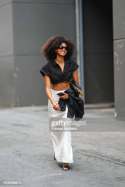 Model wears a black cropped shirt, a black leather pouch bag from Bottega Veneta, a high waist white long skirt, black sandals / shoes and holds a...