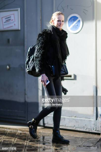 A model wears a black fur coat a black backpack black pants and black shoes outside the AALTO show during Paris Fashion Week Womenswear Fall/Winter...