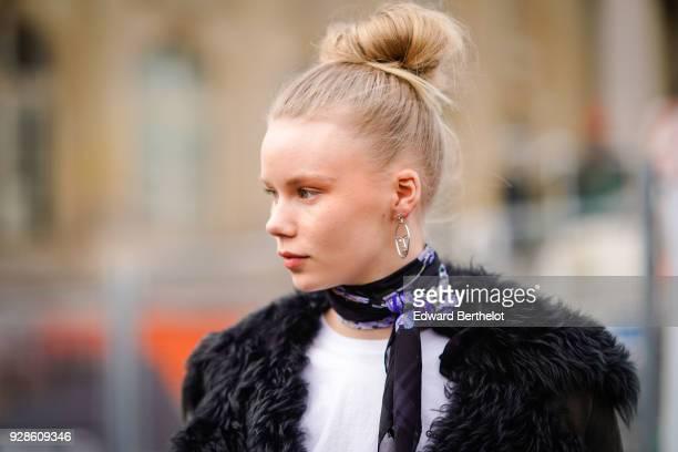 A model wears a black fur coat a scarf as a choker outside Chanel during Paris Fashion Week Womenswear Fall/Winter 2018/2019 on March 6 2018 in Paris...