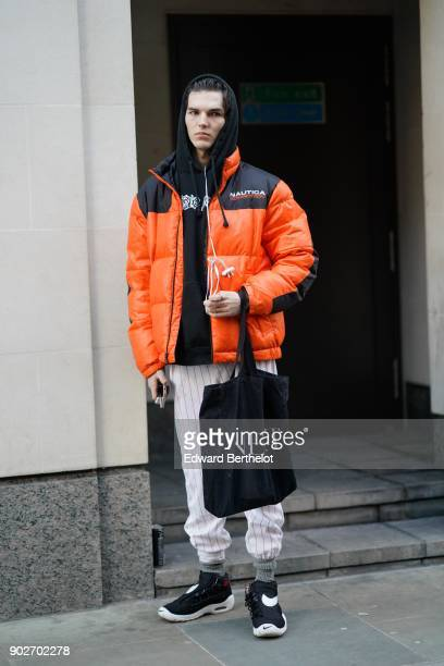 A model wears a black hoodie an orange puffer coat white pants black sneakers during London Fashion Week Men's January 2018 at on January 7 2018 in...