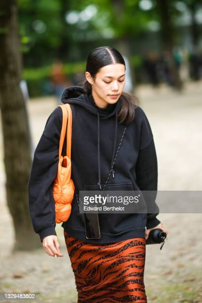 Model wears a black hoodie oversized sweater, an orange puffy shoulder bag, a black phone necklace, a black and orange zebra print pattern tube knees...