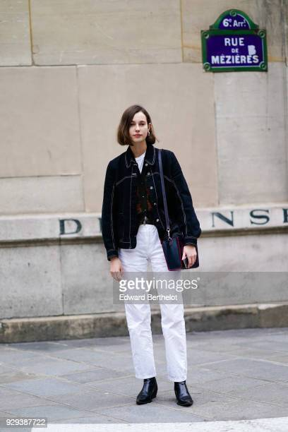 A model wears a black jacket and white pants outside APC during Paris Fashion Week Womenswear Fall/Winter 2018/2019 on March 5 2018 in Paris France