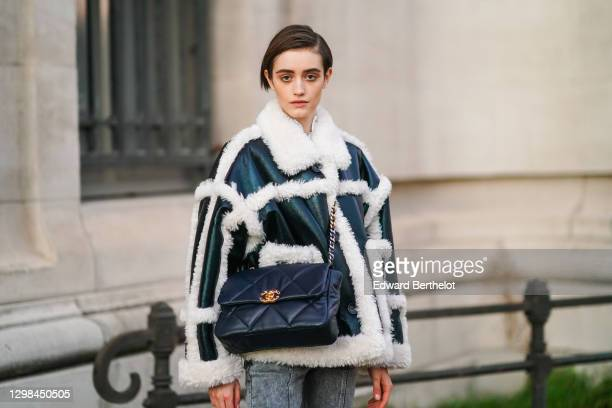 Model wears a black leather aviator winter coat with white fluffy parts, a black large leather quilted Chanel bag, gray denim jeans pants, outside...
