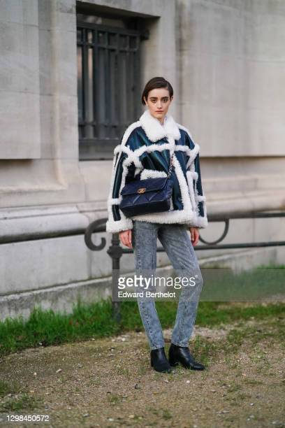 Model wears a black leather aviator winter coat with white fluffy parts, a black large leather quilted Chanel bag, gray denim jeans pants, black...