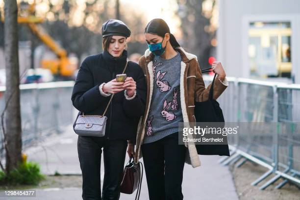 Model wears a black leather beret hat, a black puffer winter jacket, a gray quilted leather Chanel bag ; a model wears a blue and green protective...