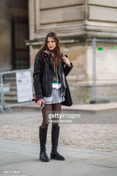 Model wears a black leather biker jacket, a red bag, a hoodie sweater, a short pleated white skirt, tights, knee-high black leather boots, on March...