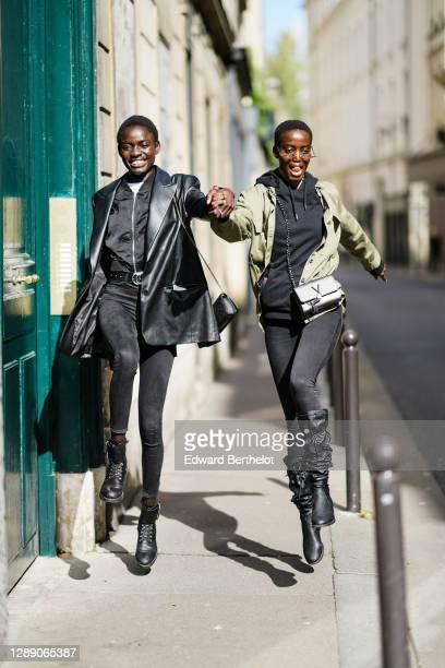 Model wears a black leather blazer jacket, a belt, black denim leggings, black leather shoes ; a model wears thunder-shaped sunglasses, a khaki...