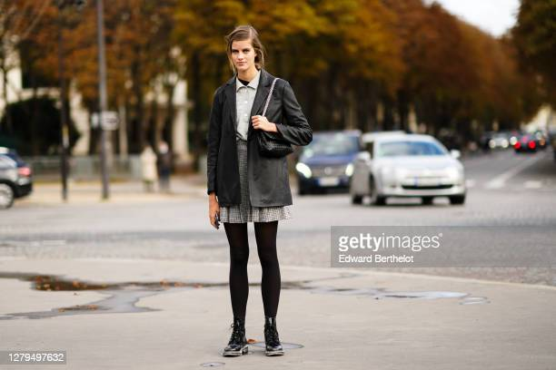 Model wears a black leather jacket, a shirt, a pleated skirt, black tights, leather shoes, a woven leather bag, outside Chanel, during Paris Fashion...