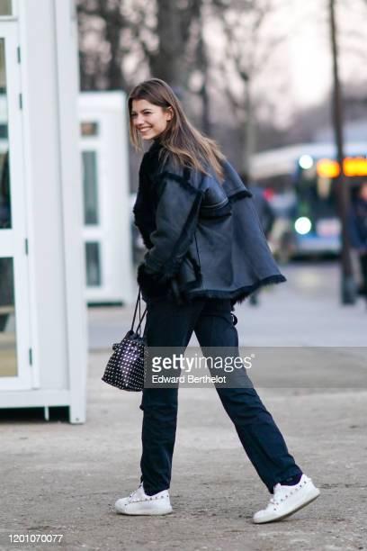 Model wears a black leather jacket, black pants, white studded sneakers, black Calvin Klein socks, a black studded bag, outside Alexandre Vauthier,...