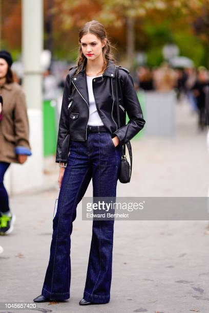 A model wears a black leather jacket blue flared jeans pants outside Chanel during Paris Fashion Week Womenswear Spring/Summer 2019 on October 2 2018...