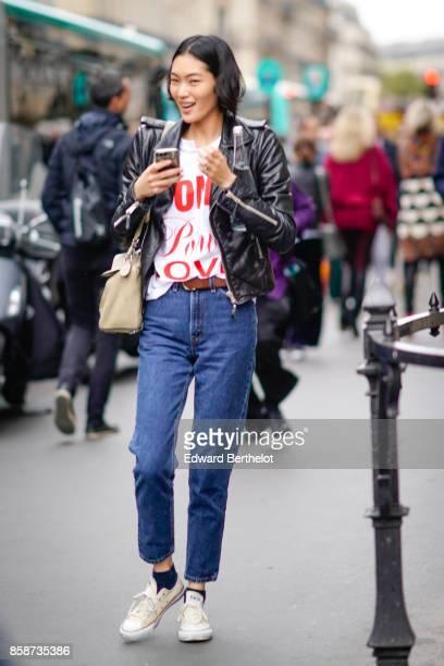 A model wears a black leather jacket blue pants white sneakers outside Stella Mccartney during Paris Fashion Week Womenswear Spring/Summer 2018 on...