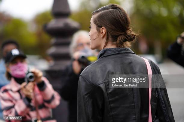 Model wears a black leather jacket, outside Chanel , during Paris Fashion Week - Womenswear Spring Summer 2021, on October 06, 2020 in Paris, France.