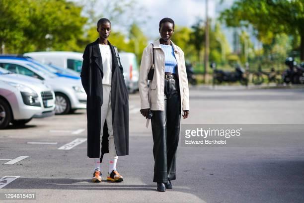 Model wears a black long wool coat, a white pullover, a necklace, sportswear cropped white jogger pants, Ellesse socks, orange Y-3 sneakers shoes ; a...