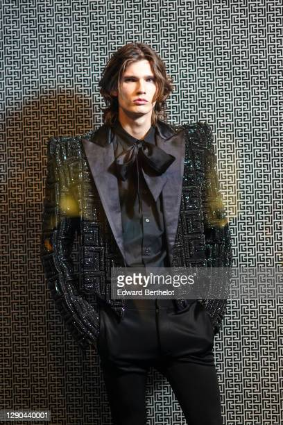 Model wears a black oversized blazer shiny glittering jacket with embroidered Balmain monograms, a bow tie, a black shirt, black suit pants, during...