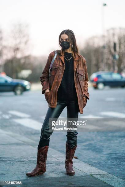 Model wears a black protective face mask, a necklace, a brown leather jacket, a black pullover, black leather pants, brown leather cowboy boots,...