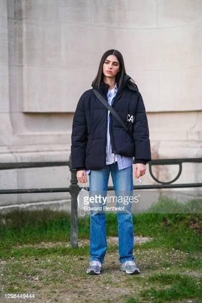Model wears a black puffer winter coat from Calvin Klein Jeans, a mauve shirt, a white t-shirt, blue denim jeans pants, New Balance sneakers shoes, a...