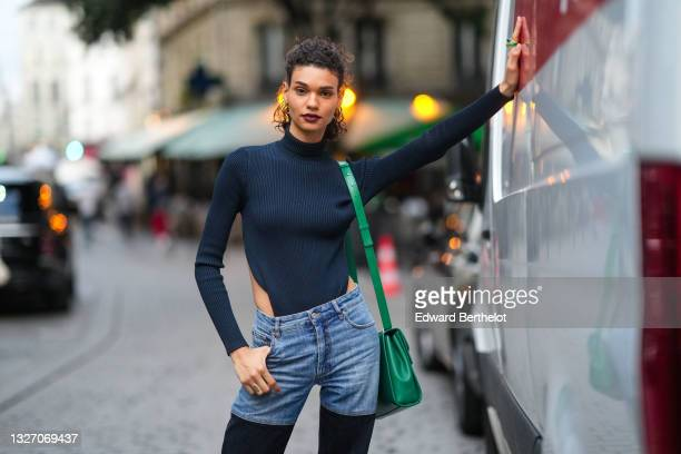 Model wears a black ribbed turtleneck cut-out body pullover, half blue faded denim hand half black denim ripped jeans pants, a yellow and green...