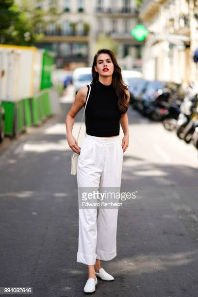 A model wears a black sleeveless top white flared pants white shoes outside JeanPaul Gaultier during Paris Fashion Week Haute Couture Fall Winter...