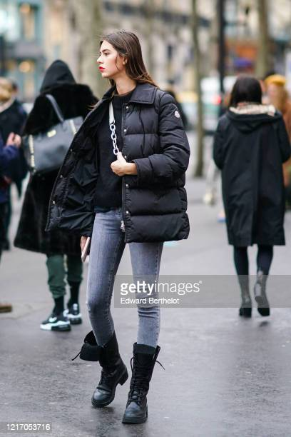 Model wears a black sweater, a black puffer jacket, blue skinny jeans, black fur-lined army-style boots, outside Ralph & Russo, during Paris Fashion...