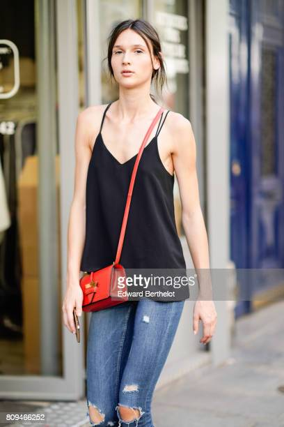 A model wears a black tank top a red bag and ripped jeans outside the Valentino show during Paris Fashion Week Haute Couture Fall/Winter 20172018 on...