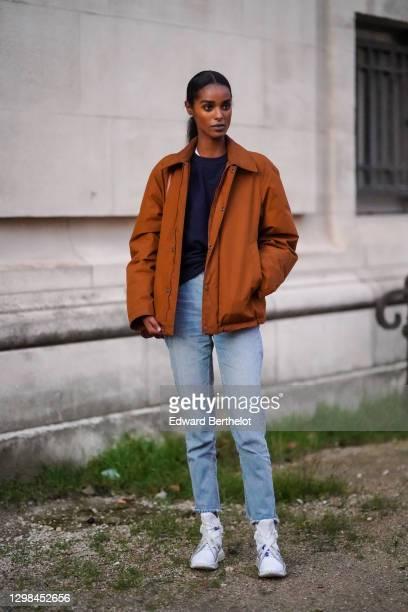 Model wears a black top, a brown winter jacket, pale blue denim jeans, white sneaker shoes, outside the Grand Palais, during Paris Fashion Week -...