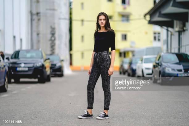 A model wears a black top gray pants sneakers during Feeric Fashion Week 2018 on July 22 2018 in Sibiu Romania