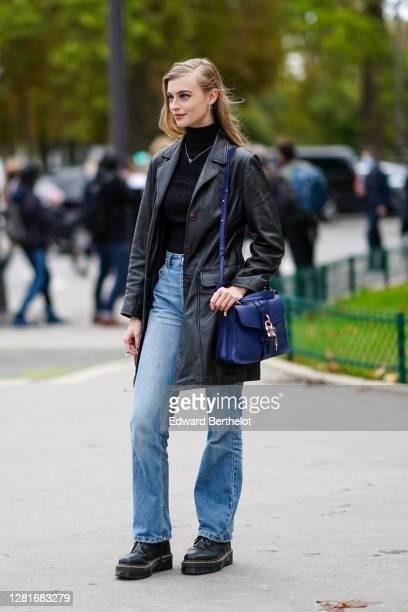 Model wears a black turtleneck pullover, a necklace, a black leather jacket, blue jeans, a blue Chloe bag with a padlock, blue denim jeans, black...