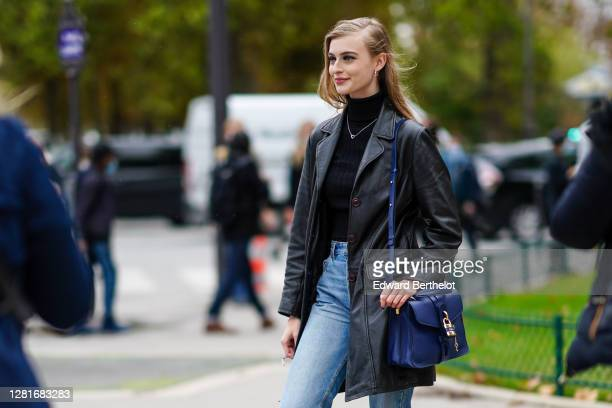 Model wears a black turtleneck pullover, a necklace, a black leather jacket, blue jeans, a blue Chloe bag with a padlock, blue denim jeans, outside...