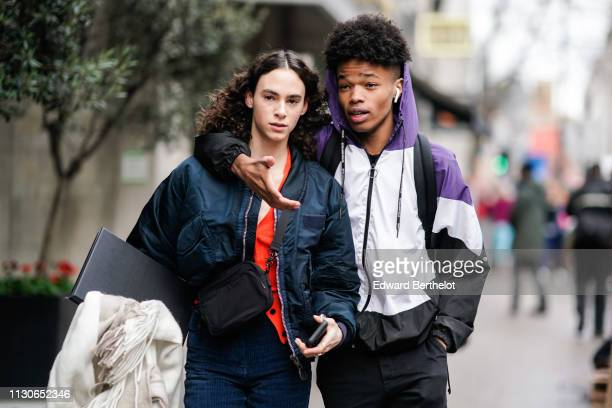 A model wears a blue bomber jacket a shoulder strapped bag a model wears a white black and purple hoodie jacket during London Fashion Week February...