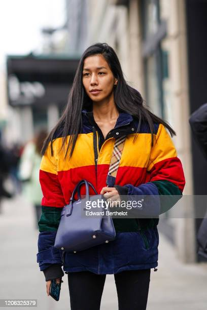 A model wears a blue Burberry leather bag a yellow/blue/red striped puffer winter jacket during New York Fashion Week Fall Winter 2020 on February 12...