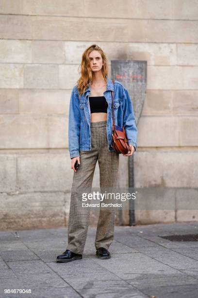 A model wears a blue denim jacket a black cropped bare belly top high waist flared pants black shoes outside Christian Dada during Paris Fashion Week...