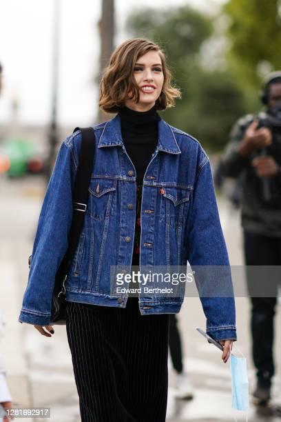 A model wears a blue denim jacket a black turtleneck pullover outside Chanel during Paris Fashion Week Womenswear Spring Summer 2021 on October 06...