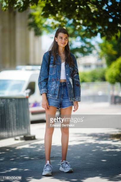 A model wears a blue denim jacket blue shorts sneakers white cropped top outside Chanel during Paris Fashion Week Haute Couture Fall/Winter 2019/2020...