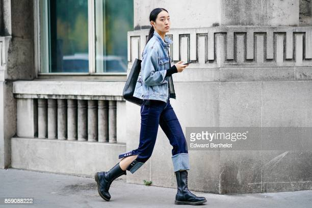 A model wears a blue denim jacket cropped pants black leather boots outside Kaviar Gauche during Paris Fashion Week Womenswear Spring/Summer 2018 on...