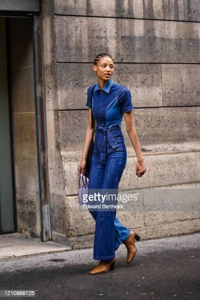 Model wears a blue denim jumpsuit , tan-color square-end boots, a mauve handbag, outside Giambattista Valli, during Paris Fashion Week - Womenswear...