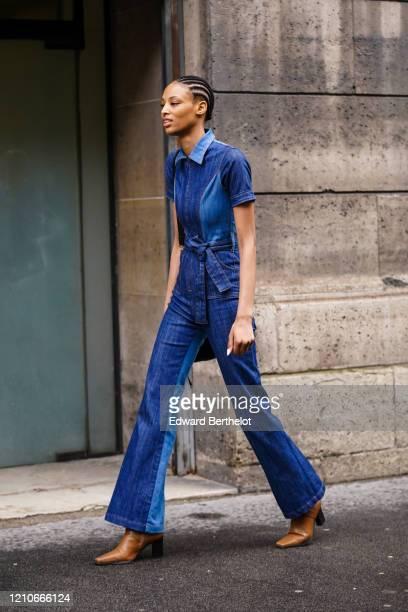 Model wears a blue denim jumpsuit , tan-color square-end boots, outside Giambattista Valli, during Paris Fashion Week - Womenswear Fall/Winter...