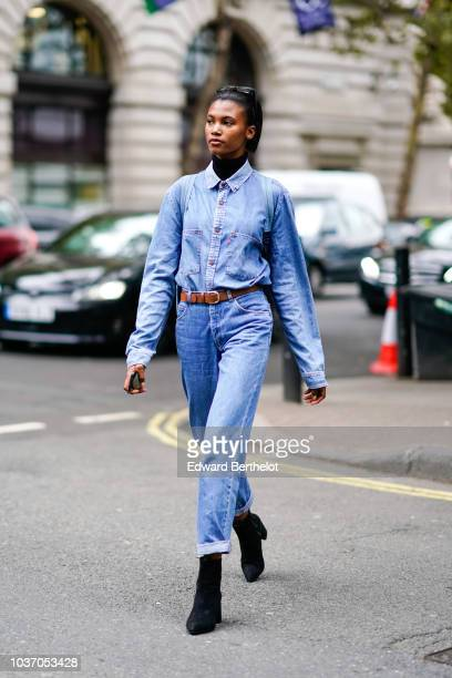A model wears a blue denim shirt a brown leather belt cropped pants black shoes during London Fashion Week September 2018 on September 14 2018 in...