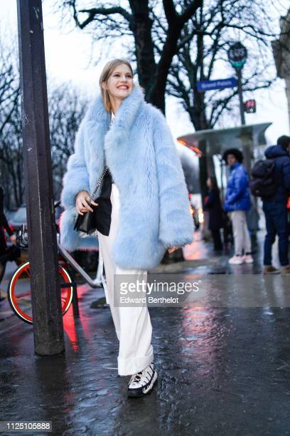 A model wears a blue faux fur winter coat white pants outside Alexandre Vauthier during Paris Fashion Week Haute Couture Spring Summer 2020 on...
