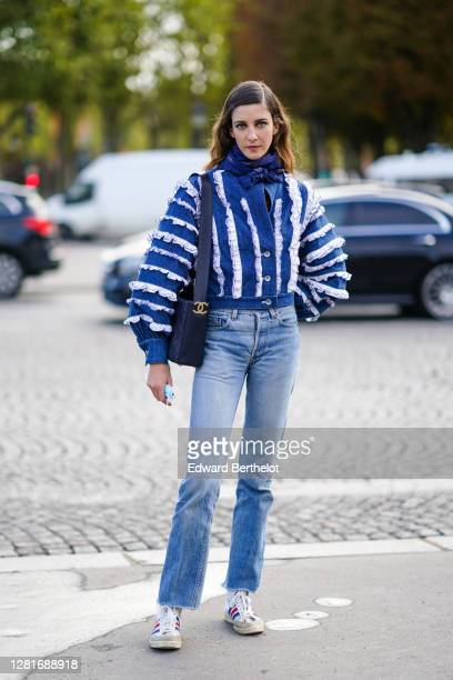 Model wears a blue scarf, a blue and white oversized denim jacket with white striped ruffles, a Chanel bag, blue denim jeans pants, sneakers, outside...