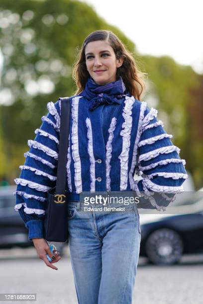 Model wears a blue scarf, a blue and white oversized denim jacket with white striped ruffles, a Chanel bag, blue denim jeans pants, outside Chanel ,...