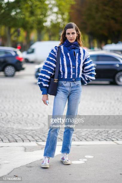 Model wears a blue scarf, a blue and white ruffled denim jacket, a Chanel bag, blue jeans, sneakers outside Chanel, during Paris Fashion Week -...
