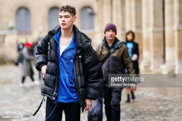A model wears a blue shirt a black puffer jacket black pants outside Thom Browne during Paris Fashion Week Menswear Fall Winter 20182019 on January...