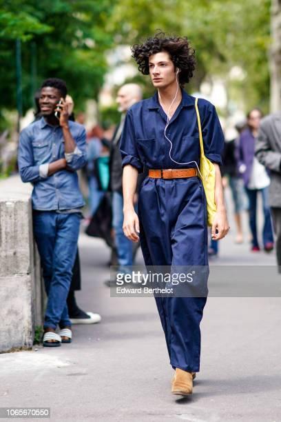 A model wears a blue shirt an orange belt pants suede shoes a yellow tote bag outside Rick Owens during Paris Fashion Week Menswear SpringSummer 2019...