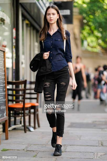 A model wears a blue shirt black ripped jeans and black sneakers outside the Valentino show during Paris Fashion Week Haute Couture Fall/Winter...