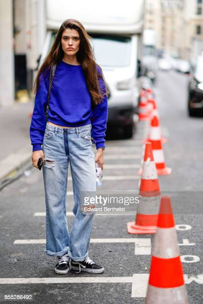 A model wears a blue top ripped jeans outside Chloe during Paris Fashion Week Womenswear Spring/Summer 2018 on September 28 2017 in Paris France