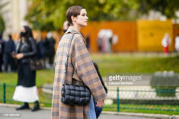 Model wears a brown and black checked long coat, a black woven leather Bottega Veneta bag, outside Chanel, during Paris Fashion Week - Womenswear...
