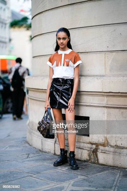 A model wears a brown and white shirt black leather skirt black leather shoes a Vuitton bag outside Valentino during Paris Fashion Week Haute Couture...